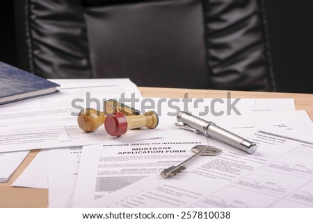 pen, key and stamps on mortgage application form - stock photo