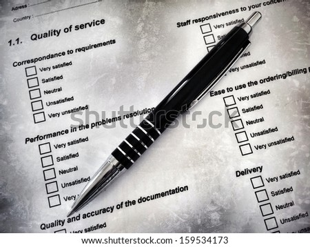 Pen laying on a customer satisfaction form, referring to concepts such as marketing survey, assessment, criteria, quality of products or services, as well as administration and form filling