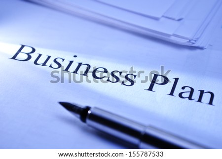 Pen lying on a document titled Business Plan conceptual of planning and strategy for improved performance and growth within a corporate business