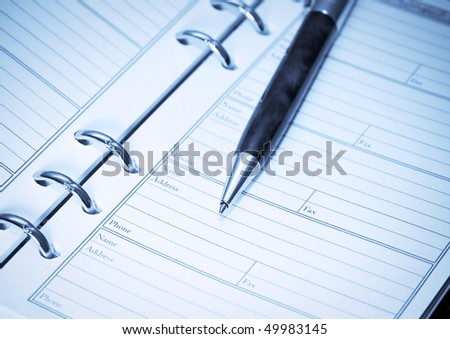pen lying on opened notebook. blue toning