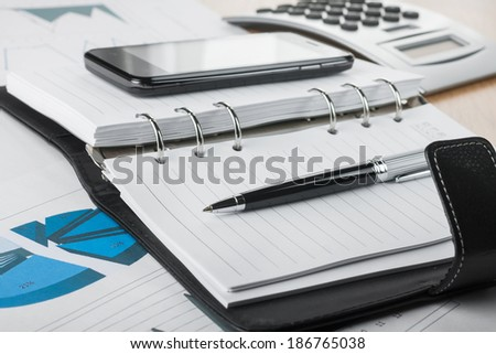 Pen lying on the diary, amid phone and calculator