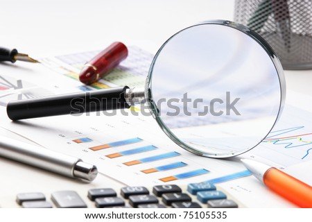 pen, magnifying glass and the working paper with a diagram