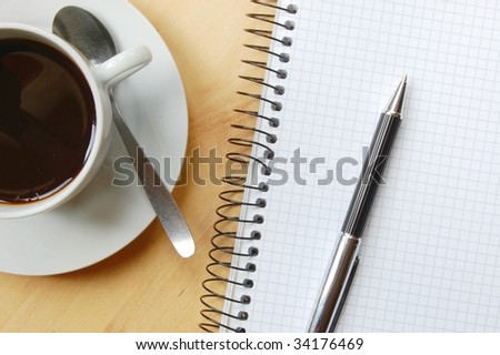 pen, notebook and cup of coffee on the desk - stock photo