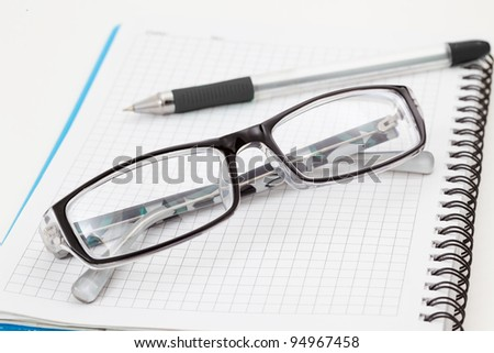 pen notebook and glasses in composition