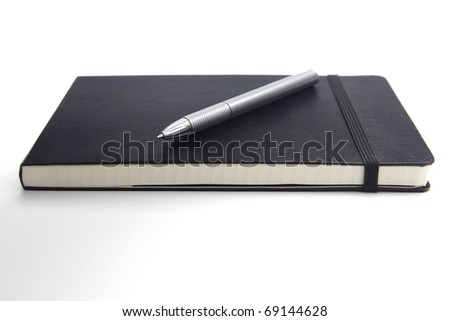 Pen on a closed notebook, isolated on white background - stock photo