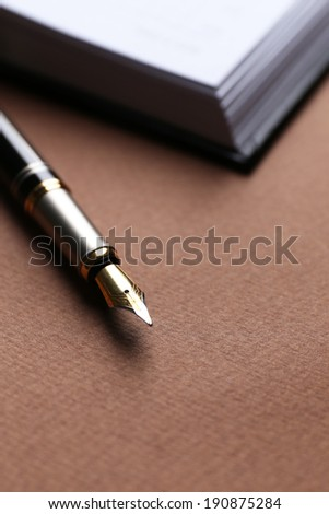Pen on book on brown table, close up