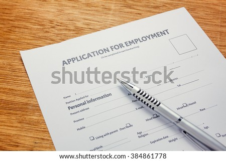 pen on business document application form and  wood background. - stock photo