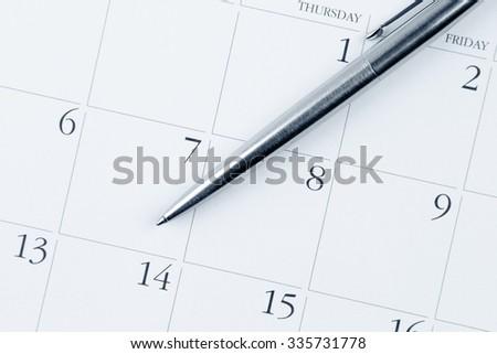 Pen on calendar page - stock photo