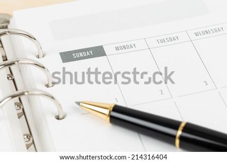 Pen on calendar page organizer notebook - stock photo