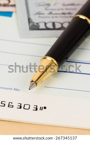 Pen on check book with money