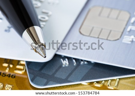 Pen on credit stack of cards - stock photo