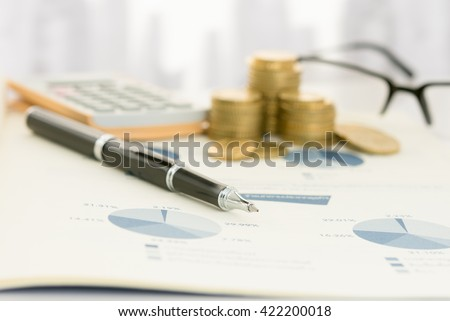 Pen on earnings report with calculator, money on table of financial adviser. Concept of invest planning, analyze return on investment. - stock photo