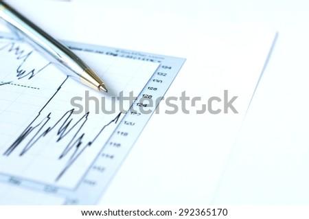 Pen on financial graph stock analysis - stock photo