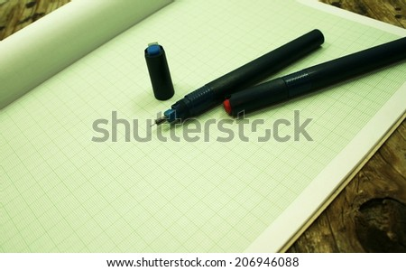 pen on green graph paper - stock photo