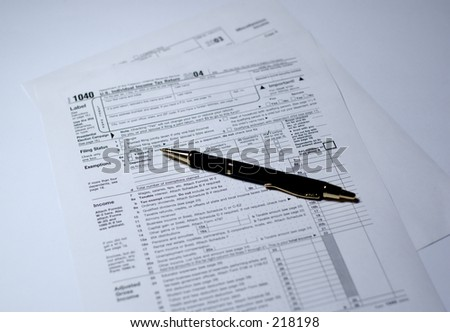 Pen on IRS forms 1040 and 1099. Shallow depth of field, focus on tip of the pen. - stock photo