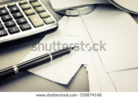 Pen on many receipts with part of paper nail and calculator for financial concept - stock photo
