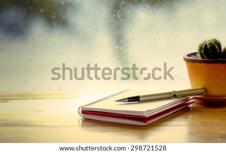 Pen on notebook on  rainy day window background  in vintage color tone - stock photo