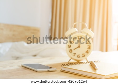 pen on notebook, smartphone alarmclock in bed room with lighting morning time selective focus and blurred background - stock photo