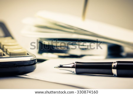 Pen on receipt with part of paper nail and calculator
