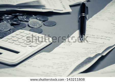 Pen on receipts with calculator and money - stock photo