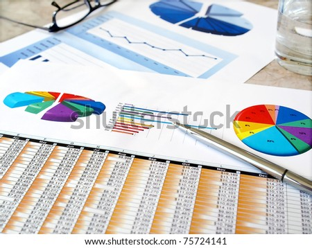 Pen on the investment charts . - stock photo