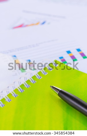 Pen on the notebook with financial graphs,Business concept.