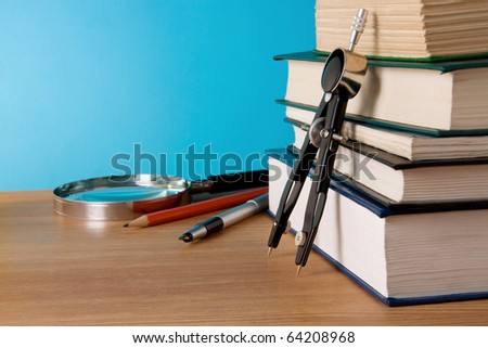 pen, pencil, pile of books and magnifier on wood table - stock photo