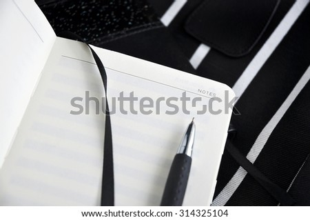 pen point to blank note page on black background - stock photo