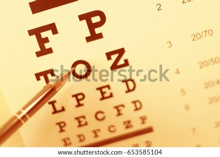 Pen pointing to letter in eyesight check table