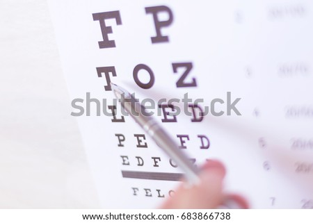Pen pointing to letter in vision check table