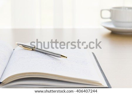 Pen put on a book with on the desk, 