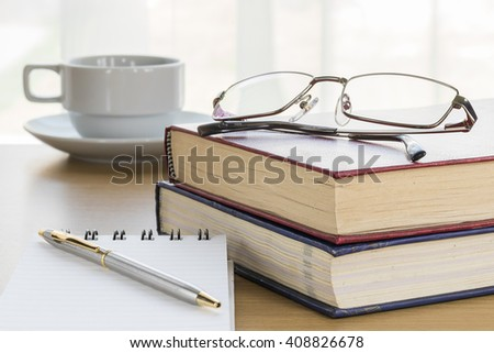 Pen put on notepad open blank page on wood table - stock photo