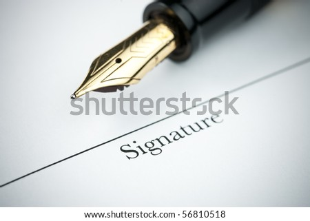 Pen resting above signature line of document. Focus on tip of pen nib. - stock photo