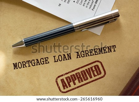 Pen rests on top of a real estate mortgage loan document. A warm color scheme dominates the image.  - stock photo
