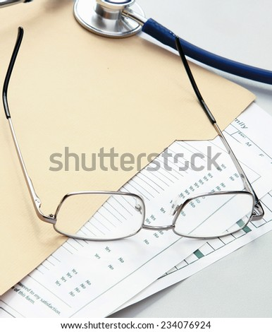 Pen ,stethoscope , folder with papers and glasses. - stock photo