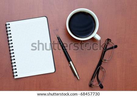 Pen, white spiral notebook and glasses with cup of coffee on the desk - stock photo