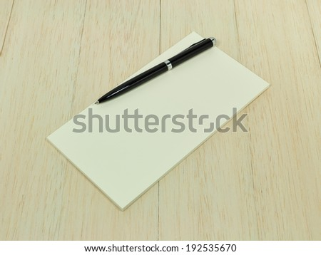 Pen with blank paper on wood table