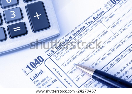 Pen with calculator over 1040 tax form with blue overlay top view