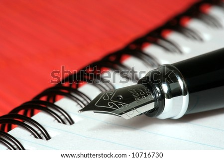 pen with notebook on red bamboo mat - stock photo
