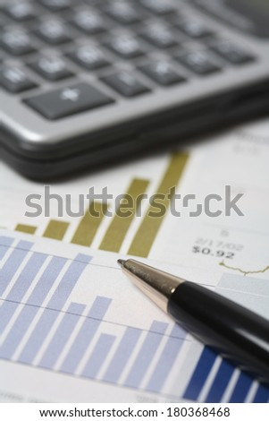 Pen with stats and graphs and calculator in background  - stock photo