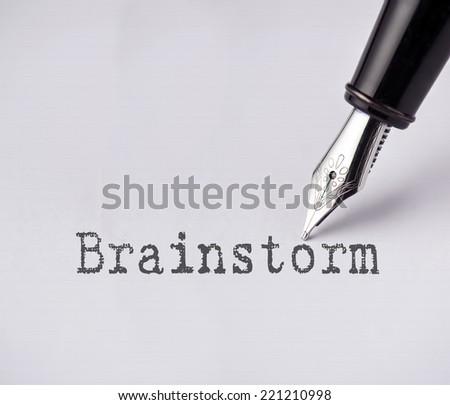 Pen writes brainstorm on paper  - stock photo