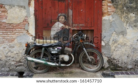 PENANG, MALAYSIA-AUG 13: General view of a mural 'Boy on a Bike' painted by Ernest Zacharevic in Penang on August 13, 2013. The mural is one of the 9 murals paintings in early 2012.  - stock photo