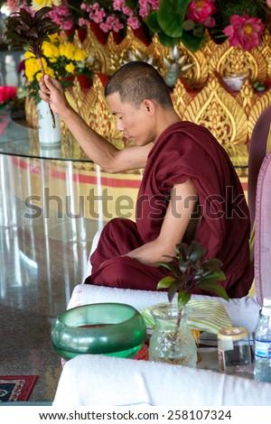 PENANG, MALAYSIA- CIRCA JAN 2015 : Buddhist monk inside the Dhammikarama, a burmese buddhist temple in Penang Malaysia during Chinese New Year 2014. - stock photo