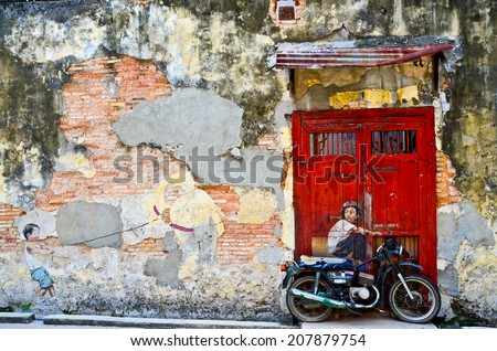 PENANG, MALAYSIA- circa  JULY 2013: Street Mural entitled 'Boy on a bike; and a boy and his kite' painted by Ernest Zacharevic in Penang. - stock photo