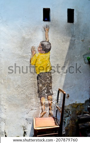 PENANG, MALAYSIA- circa JULY 2013: Street Mural entitled 'Reaching Up' painted by Ernest Zacharevic in Penang. - stock photo