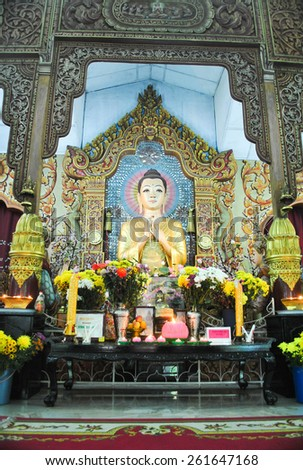 Penang, Malaysia:JULY 14, 2013: Dhammikarama Burmese  Temple Altar with Buddha and two Monks Statues. This temple is a popular tourist attraction for both locals and tourists. - stock photo