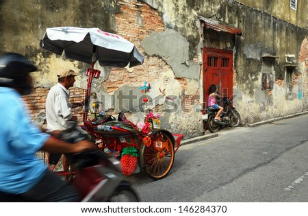 PENANG, MALAYSIA-JULY 6: Kid poses in-front of Street Mural Installation Painting tittle 'Boy on a Bike' painted by Ernest Zacharevic in Penang on July 6, 2013. - stock photo