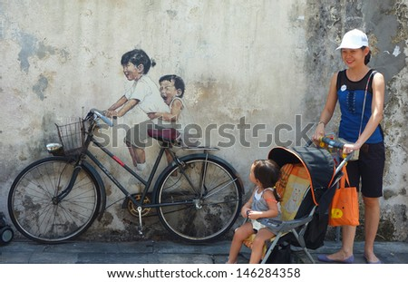 PENANG, MALAYSIA-JULY 6: Local tourist poses in-front of Street Mural tittle 'Little Children on a Bicycle' painted by Ernest Zacharevic in Penang on July 6, 2013. - stock photo