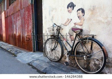 PENANG, MALAYSIA-JULY 6: Street Mural Installation Painting tittle 'Little Children on a Bicycle' painted by Ernest Zacharevic in Penang on July 6, 2013. - stock photo