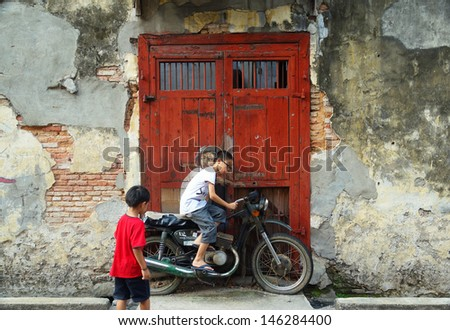 PENANG, MALAYSIA-JULY 6: Unidentified kids play with Street Mural Installation Painting tittle 'Boy on a Bike' painted by Ernest Zacharevic in Penang on July 6, 2013. - stock photo